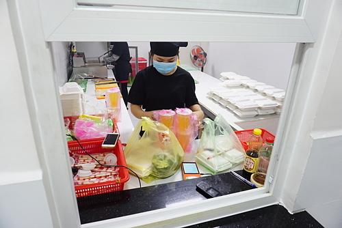 Một gian bếptrong căn bếp trung tâmtại Thủ Đức nhìn qua ô cửa giao hàng. Ảnh: Viễn Thông