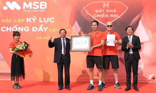 Đại diện tổ chức kỷ lục Guiness Việt Nam (trái) cho cho lãnh đạoMSB (phải)giấy chứng nhận xác lập kỷ lục đơn vị có số lượng nhân viên tham gia chống đẩy nhiều nhất tại Việt Nam.