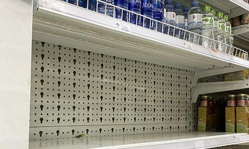 Kệ hàng chai nước loại 1,5 lít và 5 lít trong siêu thị trong một chung cư ở Linh Đàm trống trơn sáng 16/10. Ảnh: Anh Tú