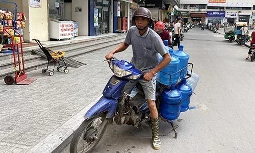 Bình nước 20 lít liên tục được chở đến các khu chung cư ở Linh Đàm, Hà Nội sáng 16/10. Ảnh: Anh Tú.