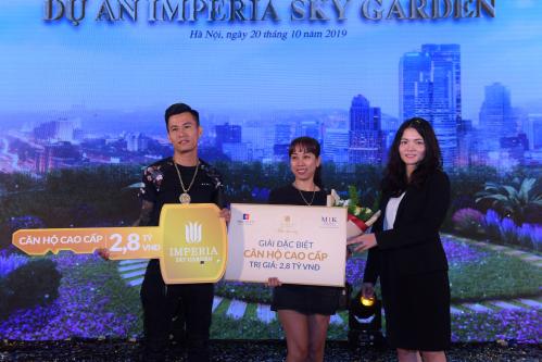 Bà Hoàng Thùy Giang (bên phải),đại diện MIKGroup trao phần thưởngcăn hộ trị giá 2,8 tỷ đồng cho vợ chồng cư dân Nguyễn Tuấn Anh.