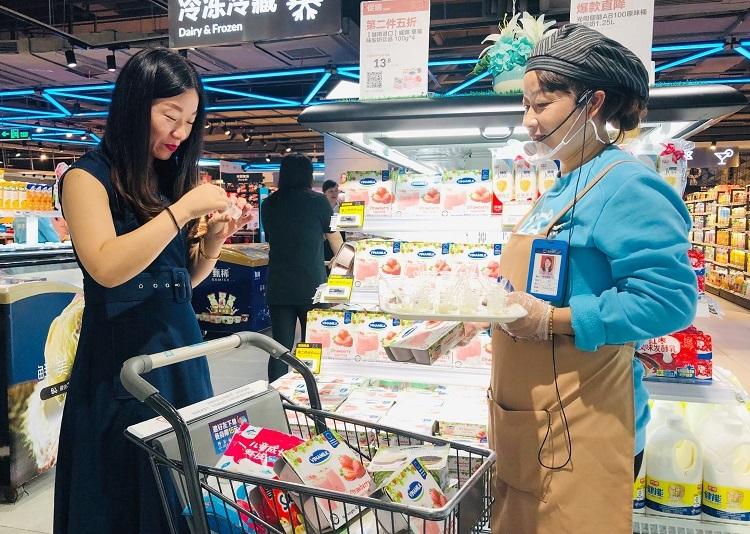 Một người dùng đang thử sữa chua Vinamilk tại siêu thị Hema.