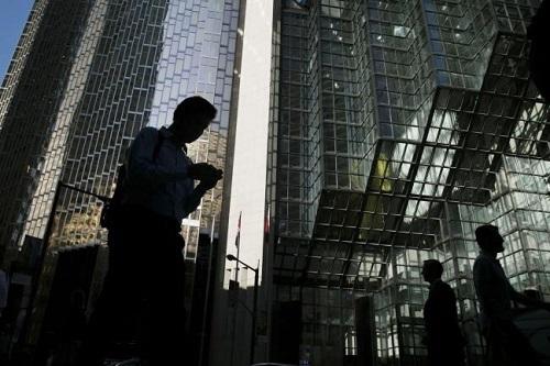 Người đi lại trước trụ sở một ngân hàng. Ảnh: Bloomberg.