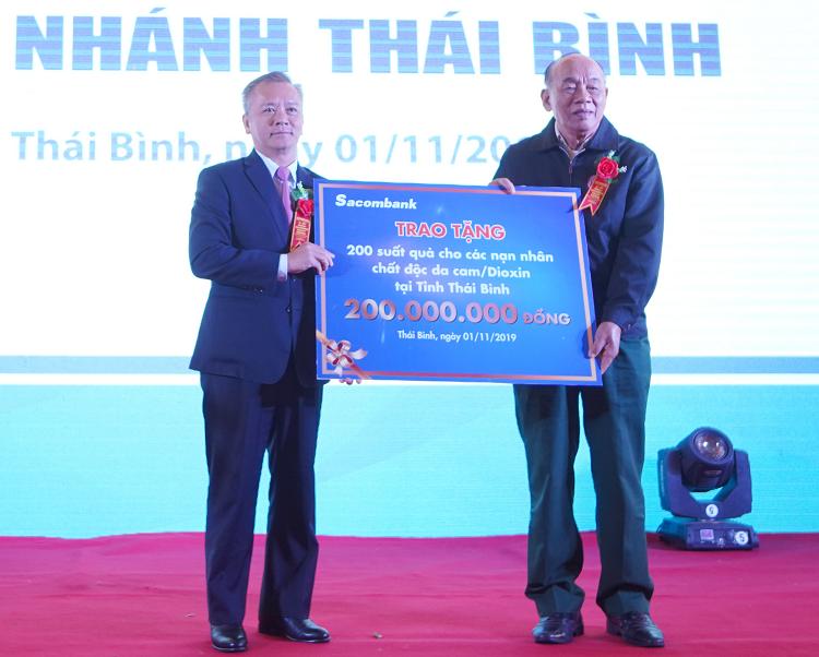 Đại diện Sacombank trao biểu trưng 200 triệu đồng tặng quà cho các nạn nhân chất độc da cam tại Thái Bình.