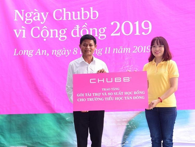 Đại diện Chubb Việt Nam (áo vàng) trao tặng gói tài trợ và học bổng cho đại diệntrường tiểu học Tân Đông. Ảnh: Chubb Life Việt Nam.