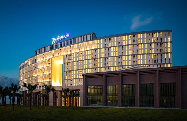Lấy cảm hứng từ cuộc sống chài lưới miền biển, khách sạn Radisson Blu Resort Cam Ranh nhìn từ xa tựa như cánh buồm no gió đang vươn mình chinh phục đại dương. Thiết kế ô thoáng khổng lồ được ví như cửa sổ đại dương bởi tầm nhìn vô cực, xuyên thấu, tưởng như thu trọn cả biển trời vào tầm mắt.