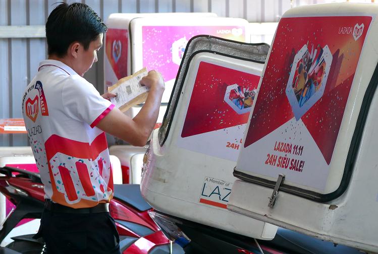 Nhân viên công ty vận chuyển hàng hóa Lazada Express (LEX) kiểm tra hàng trước khi giao. Ảnh: Quân Vũ.