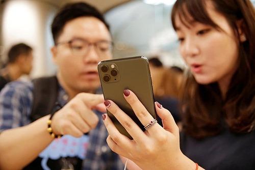 Khách hàng xem sản phẩm iPhone 11 trong một cửa hàng ở Trung Quốc. Ảnh: Reuters
