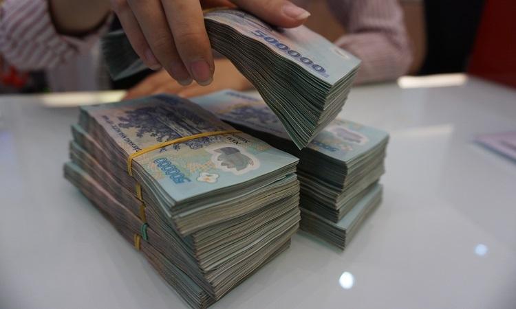 Khách gửi tiền tại ngân hàng. Ảnh: Anh Tú.