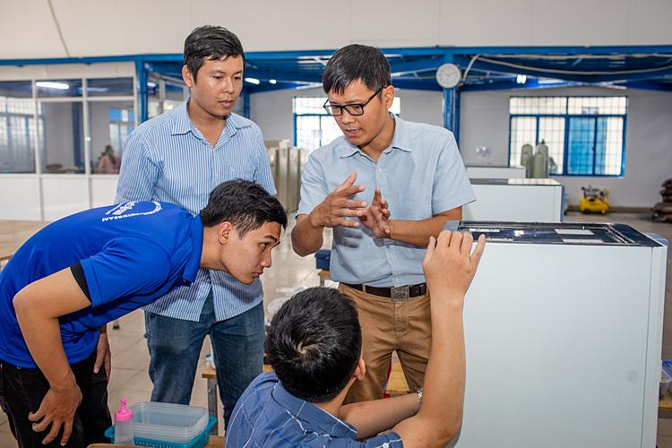 T.S Quyết đang hướng dẫn các kỹ sư lắp đặt máy tại xưởng. Ảnh: Thành Nguyễn.