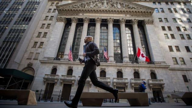 Một người đàn ông chạy ngang qua Sở giao dịch chứng khoán New York. Ảnh: Bloomberg
