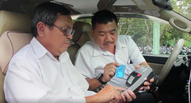 Hành khách thanh toán trên taxi Vinasun. Ảnh: Phương Đông.