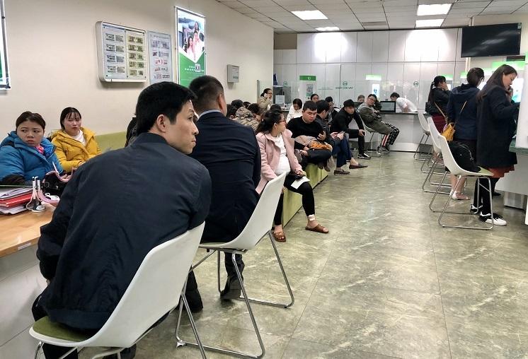 Khoảng một nửa khách đang ngồi chờ tại một góc phòng giao dịch ngân hàng trên đường Duy Tân, Cầu Giấy, Hà Nội. Ảnh: Quỳnh Trang.