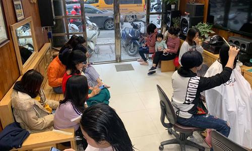 Một tiệm tóc rất đông khách ngồi chờ ngay khi mới mở cửa hàng. Ảnh: NT