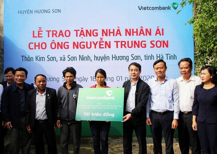 Ông Nghiêm Xuân Thành - Chủ tịch HĐQT Vietcombank (thứ tư từ phải sang) trao số tiền ủng hộ xây nhà nhân ái cho hộ gia đình ông Nguyễn Trung Sơn tại thôn Kim Sơn, xã Sơn Ninh.