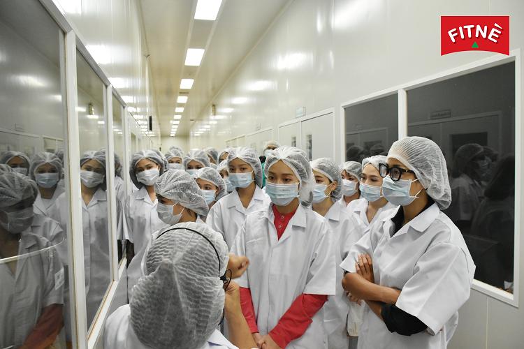 Khả Ngân (áo đỏ bên trong) cùng các đại lý được đại diệnFitne giới thiệu về nhà máy.