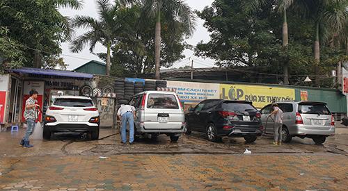 Tiệm rửa xe báo giá 200.000 đồng một lầnrửa ôtô, song vẫn kín khách với nhiều người ngồi chờ trong sáng ngày 29 Tết. Ảnh: Minh Châu