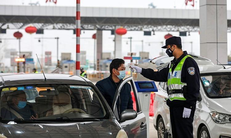 Cảnh sát Vũ Hán kiểm tra thân nhiệt của một tài xế. Ảnh: AP