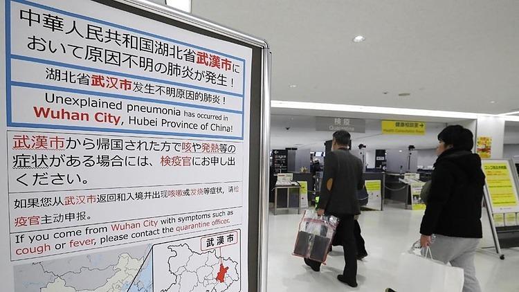Bảng thông báo về lưu ý biểu hiện bất thường đối với hành khách đến từ Vũ Hán (Trung Quốc) tại sân bay Narita (Nhật Bản). Ảnh: AFP