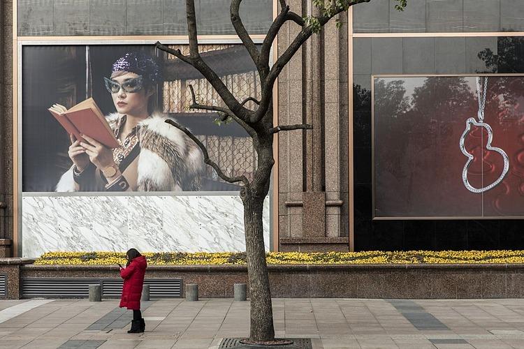 Một người phụ nữ trênđường Nam Kinh vắng lặng trong tuần này, nơi vốn làcon phố thương mại sầm uất ở Thượng Hải. Ảnh: Bloomberg