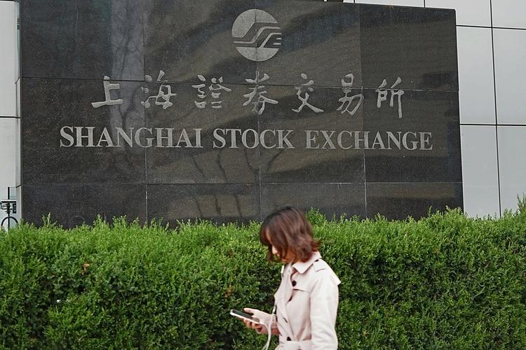 Một người đi đường đi ngang qua Sở giao dịch chứng khoán Thượng Hải. Ảnh: China Daily