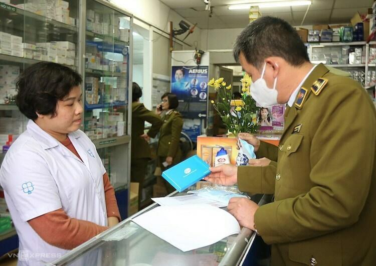 Cán bộ quản lý thị trường kiểm tra giá bán khẩu trang y tế tại một nhà thuốc ở Hà Nội. Ảnh: Ngọc Thành