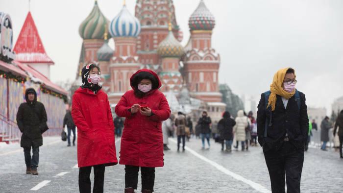 Du khách đeo khẩu trang bên ngoài điện Kremlin (Nga). Ảnh: Bloomberg