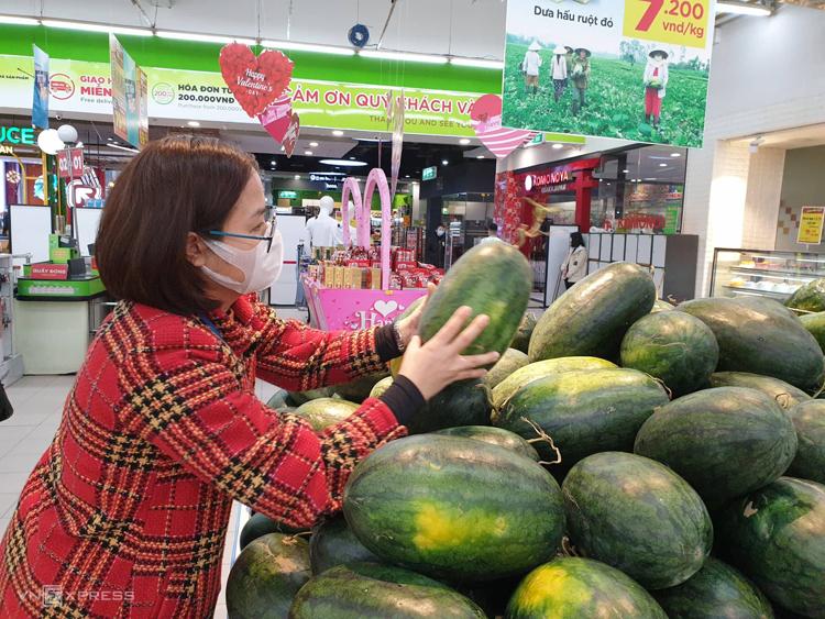 Một khách hàng chọn mua dưa hấu trong chương trình giải cứu cùng nông dân, giá 7.200 đồng một kg tại hệ thống BigC Hà Nội. Ảnh: Anh Minh