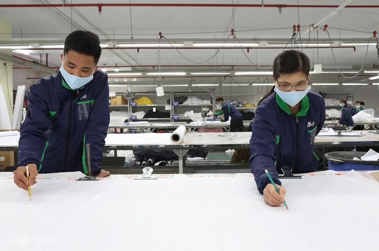 Hoạ sĩ vẽ chi tiết và kích thước khẩu trang lên từng tấm vải rồi đưa vào máy cắt. Ảnh: Ngọc Thành.