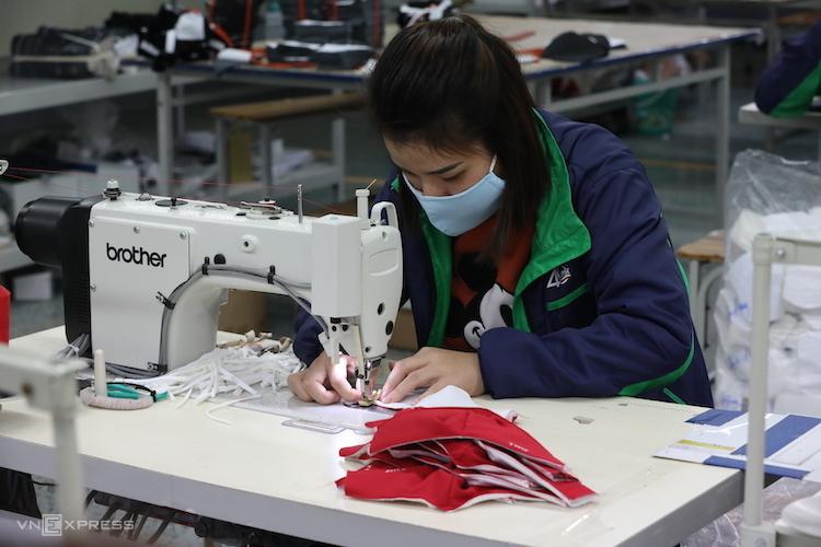 Nữ công nhân Công ty cổ phần Đầu tư & Thương mại TNG (Thái Nguyên) sản xuất khẩu trang từ vải nano kháng khuẩn. Ảnh: Ngọc Thành