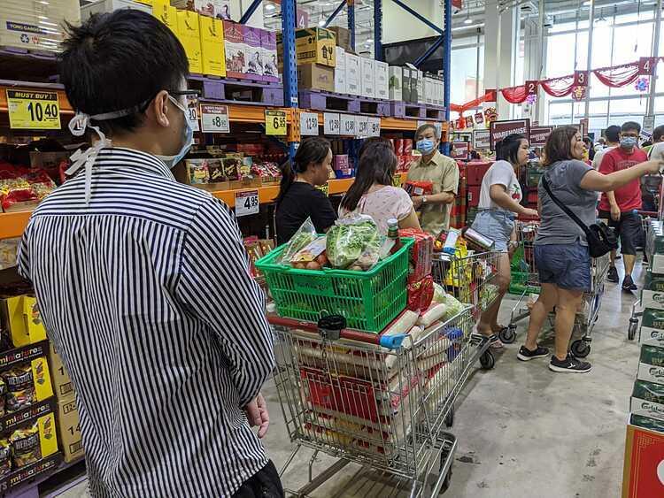 Khách hàng chờ tính tiền với 16 bao gạo trong xe đẩy tại siêu thị FairPrice. Ảnh: ST