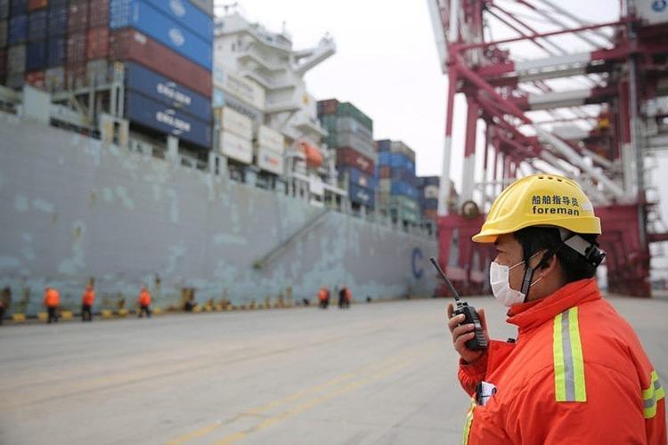 Một quản đốcđeo khẩu tranglàm việc trước một tàu chở hàng cập cảngThanh Đảo, tỉnh Sơn Đông, Trung Quốc hôm 4/2. Ảnh: Reuters