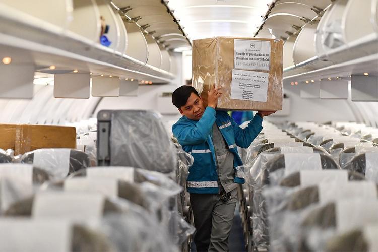 Vận chuyển hàng cứu trợ lên chuyến bay đón công dân Việt từ Vũ Hán về nước. Ảnh: VNA.