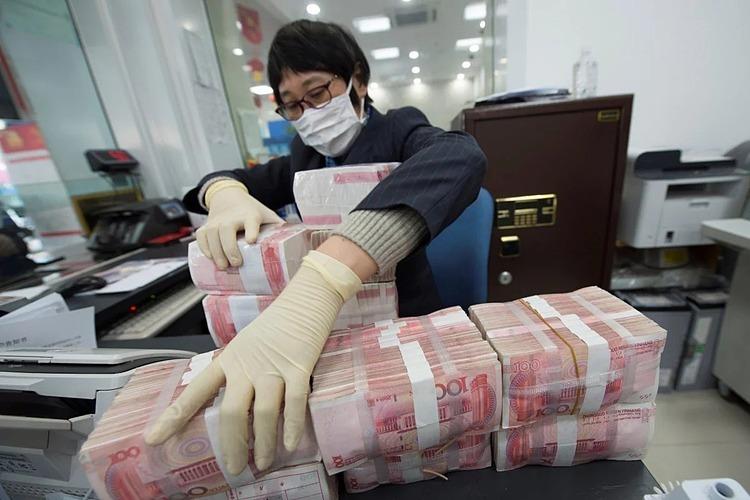 Nhân viên ngân hàng tại Trung Quốc đeo khẩu trang và găng tay khi tiếp xúc với tiền mặt. Ảnh: Reuters