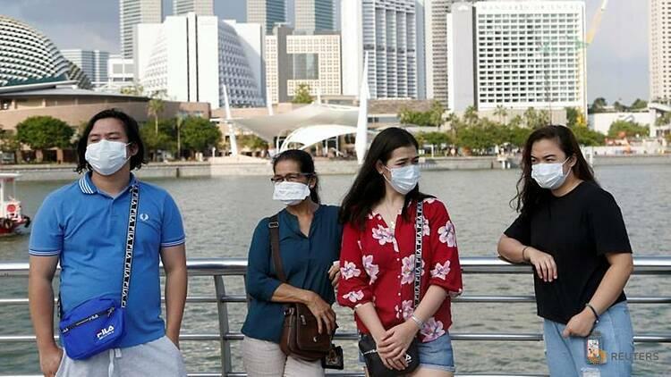 Khách du lịch đeo khẩu trang tại Singapore. Ảnh: Reuters