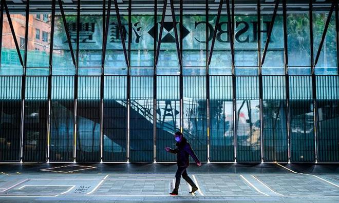 Một người đeo khẩu trang đi bộ trước ngân hàng HSBC tại Hong Kong. Ảnh: CNN