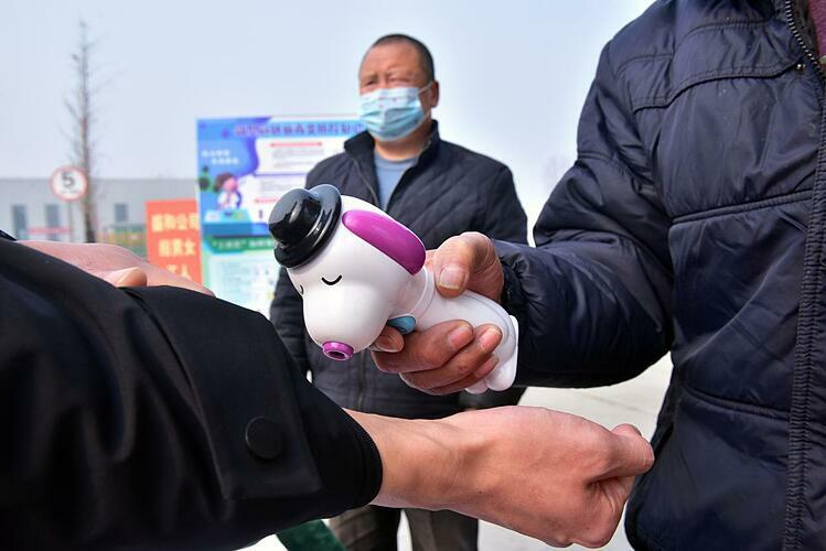 Một công nhân được kiểm tra thân nhiệt trước khi vào nhà máy ở Hà Bắc (Trung Quốc). Ảnh: Reuters