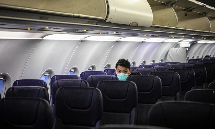 Hành khách Trung Quốc đeo khẩu trang trên một chuyến bay. Ảnh: SCMP