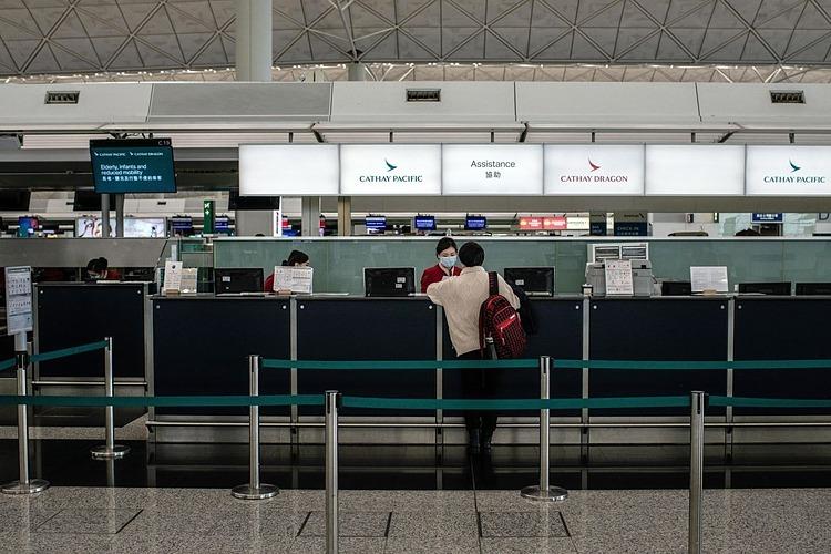 Nhân viên của Cathay Pacific nói chuyện với một hành khách tại sân bay quốc tế Hong Kong vào tháng 2/2020. Ảnh: Bloomberg