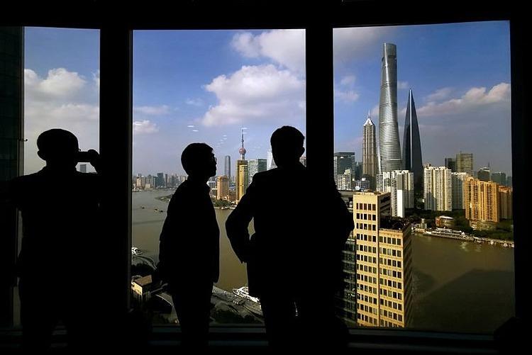 Người dân nhìn quận tài chính của Thượng Hải qua cửa kính. Ảnh: Reuters