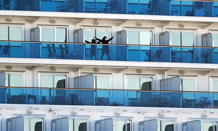 Một du khách tập thể dục ở ban công du thuyền Diamond Pricess đang bị cách ly ở cảng Yokohama. Ảnh: Reuters