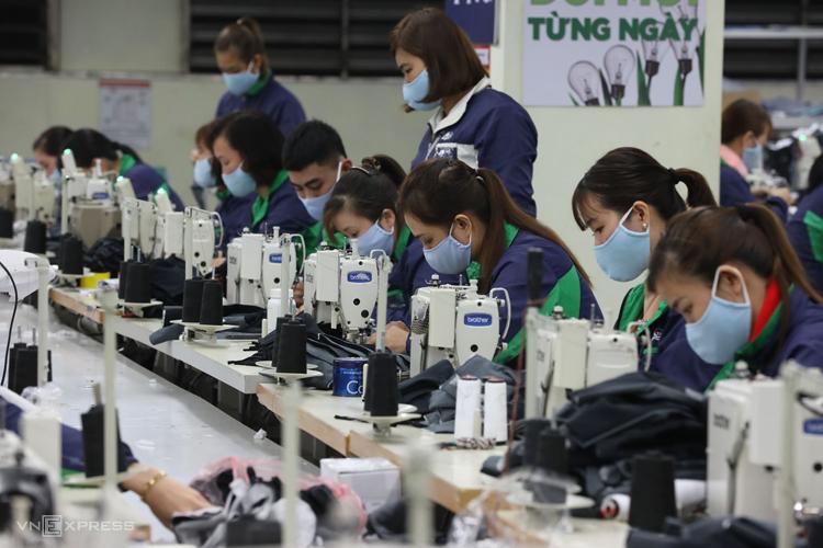 Công nhân dệt may cấp tập sản xuất khẩu trang phòng dịch. Ảnh: Ngọc Thành.
