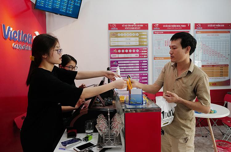 Một khách hàng mua vé Vietlott tại đại lý trên phố Trung Kính, Hà Nội.