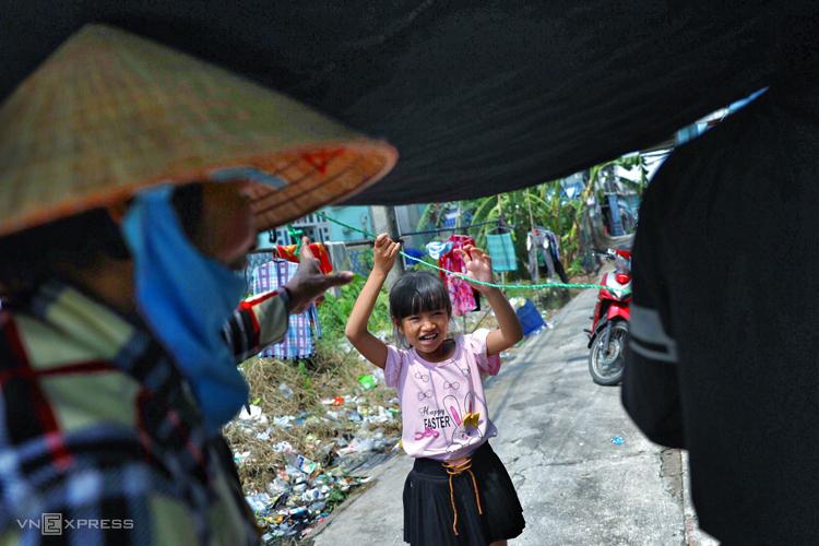 Bé Nguyễn Thanh Tiền phụ bà nội che tấm bạt che mưa trước căn nhà trọ.Ảnh: Hữu Khoa.