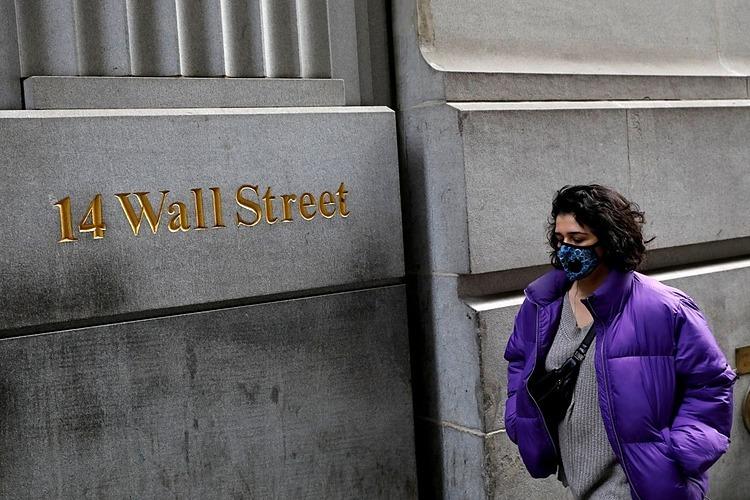 Một người đeo khẩu trang đi bộ dọc theo phố Wall, New York. Ảnh: Reuters