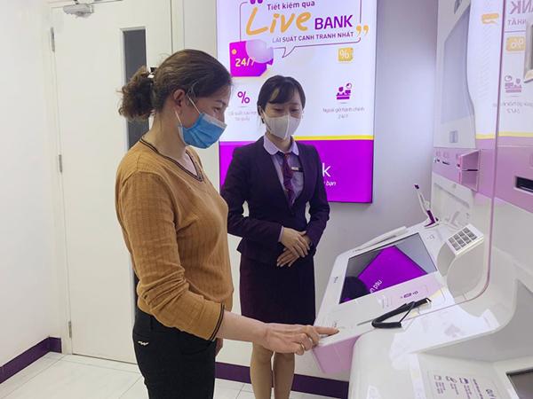 Nhân viên TPBank hỗ trợ khách hàng giao dịch tại một LiveBank.