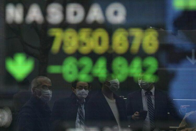 Người dân đi qua bảng điện tử của một công ty chứng khoán tại Nhật Bản. Ảnh: Reuters