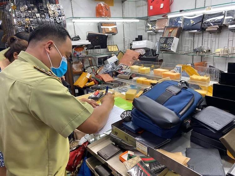 Cán bộ quản lý thị trường lập biên bản khi kiểm tra một quầy hàng tại Saigon Square (TP HCM) ngày 12/3. Ảnh: Linh Linh