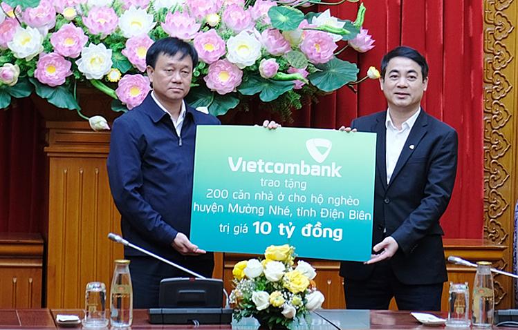 Ông Nghiêm Xuân Thành - Chủ tịch HĐQT Vietcombank (bên phải) trao biển tượng trưng 10 tỷ đồng kinh phí ủng hộ thực hiện chủ trương xây dựng, sửa chữa nhà cho 200 hộ nghèo tại huyện Mường Nhé, tỉnh Điện Biên.