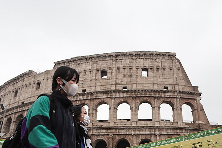Một dukhách đeo khẩu trang bên ngoàiĐấu trường La Mã (Rome)hôm 1/2. Ảnh: AFP